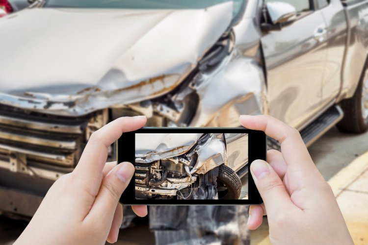 woman using smartphone to take photo of damage after car accident